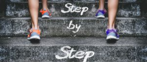 A photographic representation of people walking up the  stairs in sneakers tells the reader to keep going.