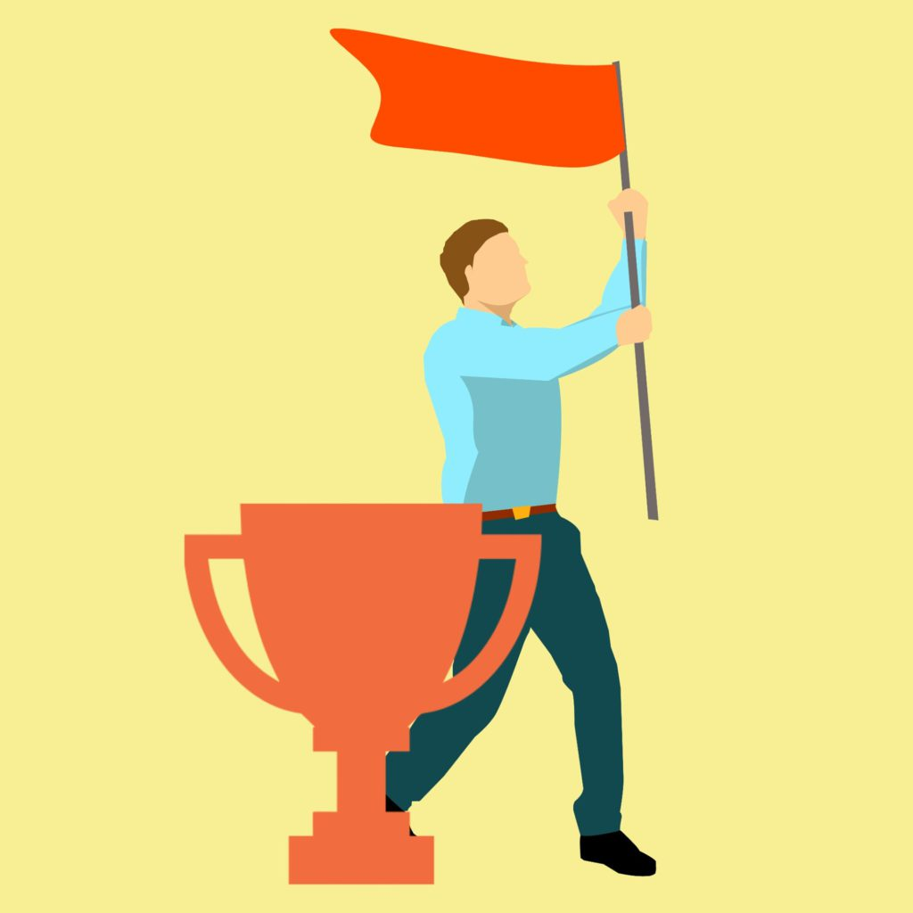man holding a flag proudly, standing next to a trophy