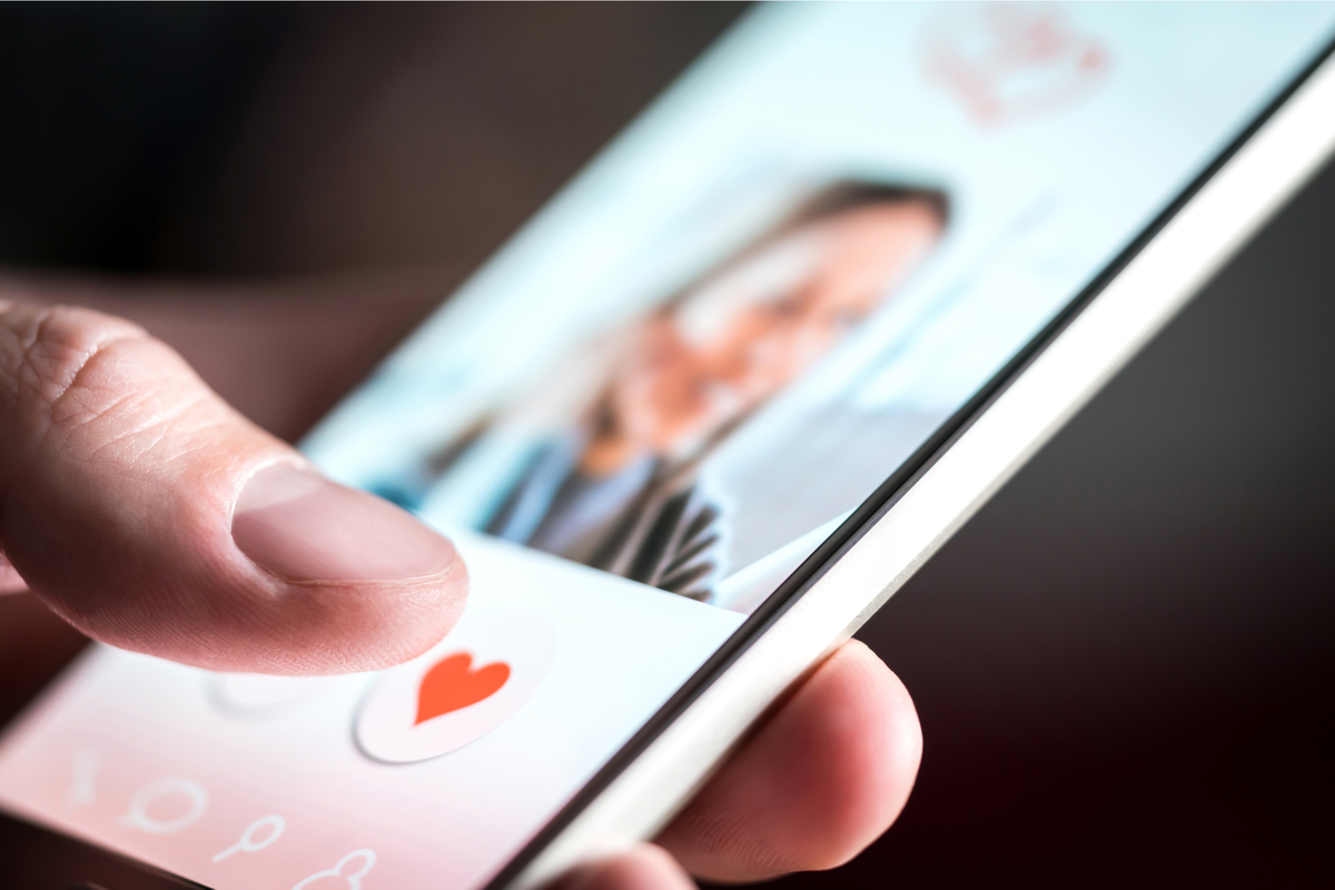 A cellphone screen with a picture of a woman and a heart.